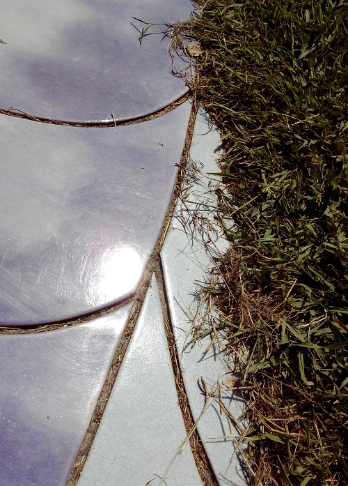 Ceramic curves embedded within the grass seem to entrap the sky
