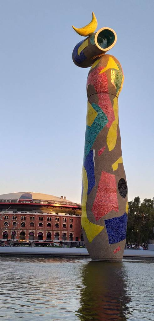 Miró's Woman and Bird on a summer's evening, showing the Arenas complex in the background